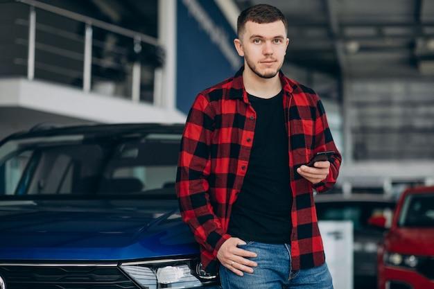Jonge mens die een auto in een autotoonzaal kiest