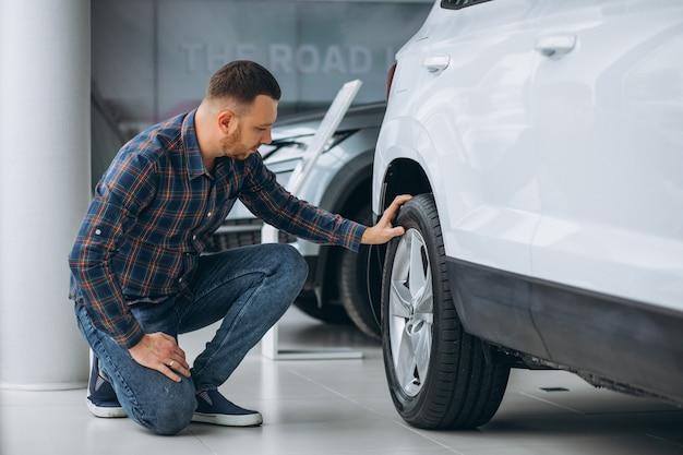 Jonge mens die een auto in een autotoonzaal koopt