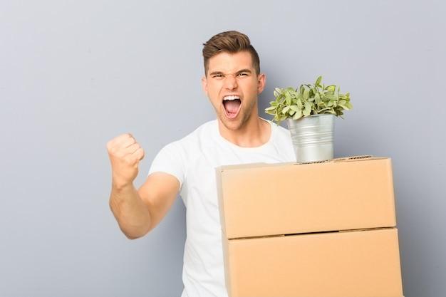 Jonge mens die een beweging doet die dozen onbezorgd en opgewekt toejuicht. overwinning concept.