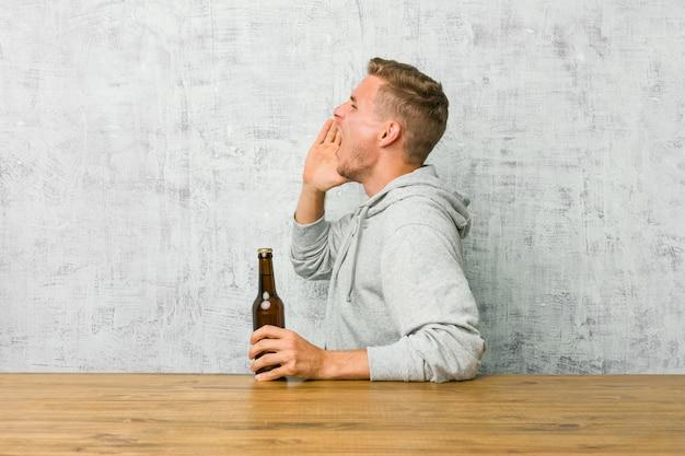 Jonge mens die een bier op een lijst drinkt die en palm schreeuwt dichtbij geopende mond houdt.