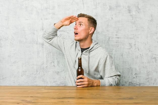 Jonge mens die een bier op een lijst drinkt die ver weg houdend hand op voorhoofd kijkt.