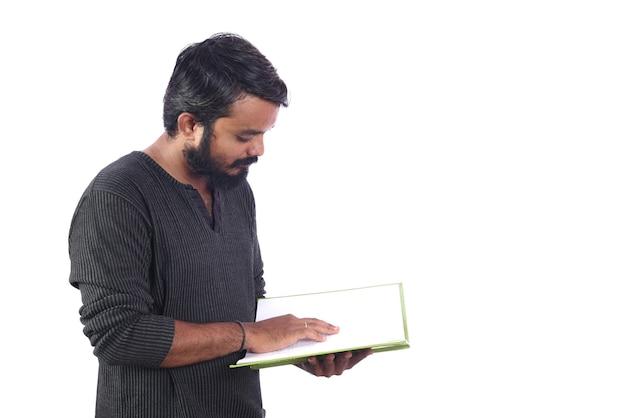 Jonge mens die een boek of een dagboek leest of houdt die op witte muur wordt geïsoleerd.