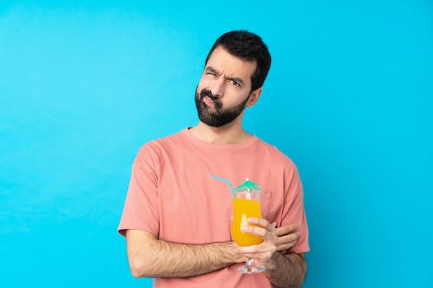 Jonge mens die een cocktail over geïsoleerde blauwe muur houden verstoord voelen