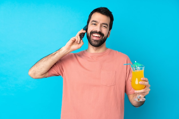 Jonge mens die een cocktail over geïsoleerde blauwe muur houdt over een gesprek met de mobiele telefoon met iemand houdt