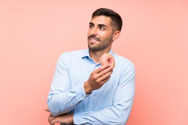 Jonge mens die een doughnut over geïsoleerde roze muur houdt die omhoog terwijl het glimlachen kijkt