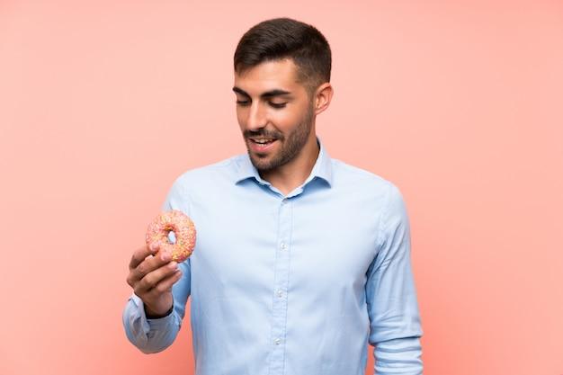 Jonge mens die een doughnut over geïsoleerde roze muur houdt die veel glimlacht