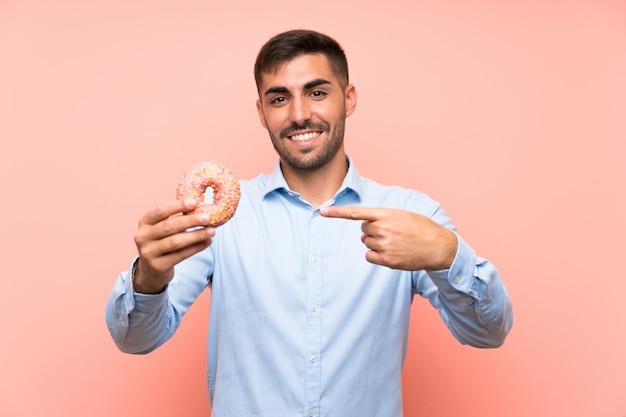 Jonge mens die een doughnut over geïsoleerde roze muur houdt