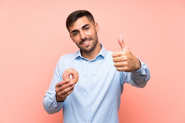 Jonge mens die een doughnut over geïsoleerde roze muur met omhoog duimen houdt omdat iets goeds is gebeurd