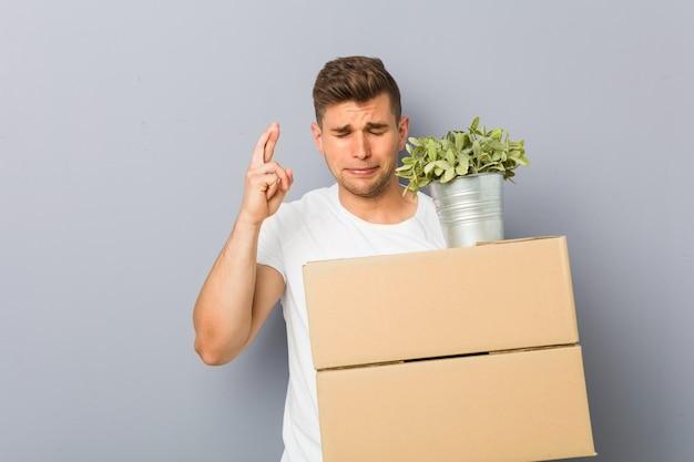 Jonge mens die een dozen van de bewegingsholding doet die vingers voor het hebben van geluk kruisen
