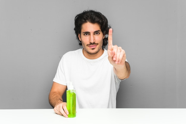 Jonge mens die een fles van aloëvera houdt die nummer één met vinger toont.