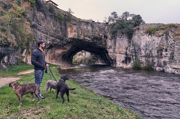 Jonge mens die een gang met zijn honden langs de bank van riviernela neemt in burgos, spanje