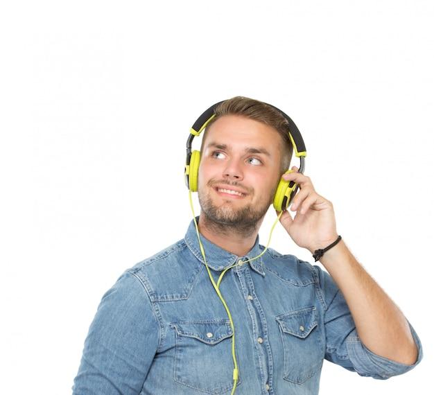 Jonge mens die een geïsoleerde oortelefoon met behulp van