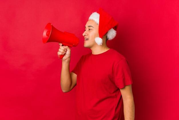Jonge mens die een gift op kerstmisdag houdt