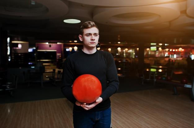 Jonge mens die een kegelenbal houdt die zich tegen kegelbanen bevindt met ultraviolet licht.