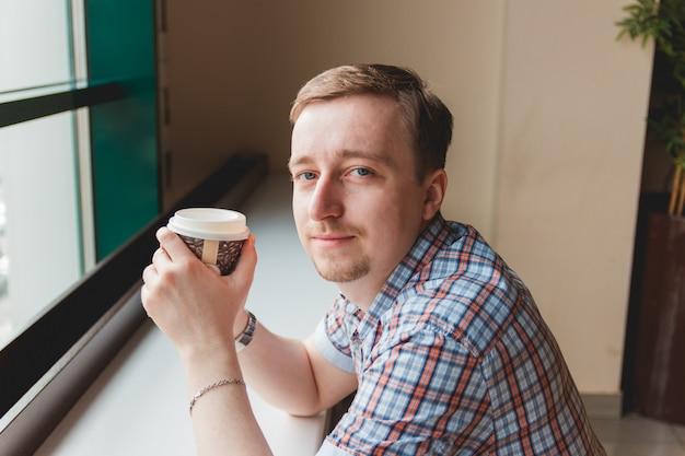 Jonge mens die een koffiepauze neemt bij koffie