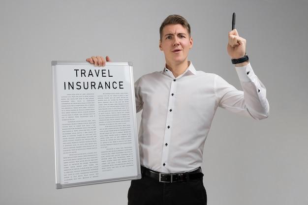 Jonge mens die een lijst van de reisverzekering houdt die op lichte achtergrond wordt geïsoleerd