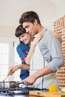 Jonge mens die een maaltijd in keuken voorbereidt