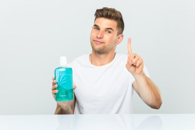 Jonge mens die een mondspoeling houdt die nummer één met vinger toont.