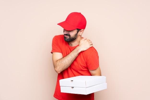 Jonge mens die een pizza houdt die aan pijn in schouder lijdt omdat hij een inspanning heeft gedaan