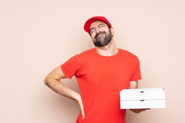 Jonge mens die een pizza houdt die aan rugpijn lijdt omdat hij zich heeft ingespannen