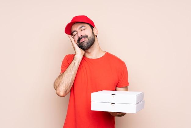Jonge mens die een pizza houdt die slaapgebaar in aanbiddelijke uitdrukking maakt