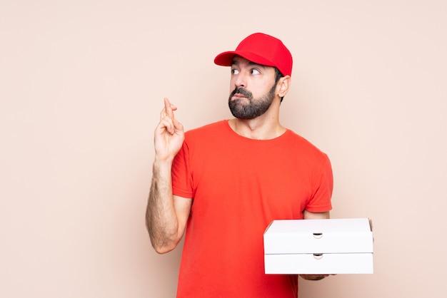 Jonge mens die een pizza met vingers houdt die en het beste kruisen wensen