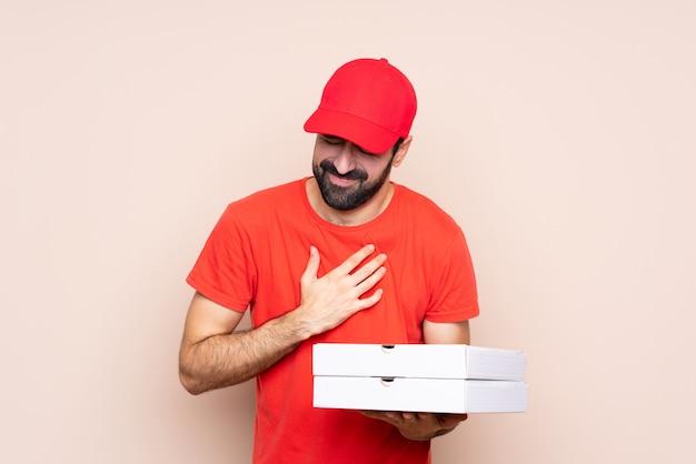 Jonge mens die een pizza over geïsoleerde achtergrond houdt die een pijn in het hart heeft