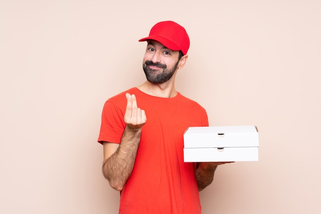 Jonge mens die een pizza over geïsoleerde achtergrond houdt die geldgebaar maakt