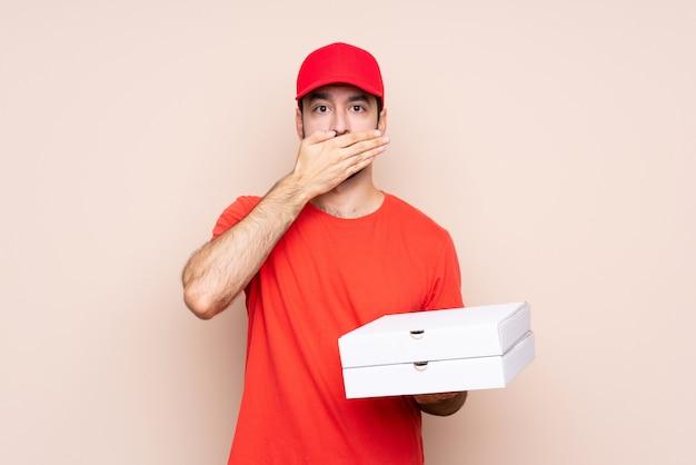 Jonge mens die een pizza over geïsoleerde achtergrond houdt die mond behandelt met handen