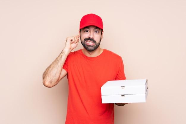 Jonge mens die een pizza over geïsoleerde gefrustreerde en het behandelen van oren houdt