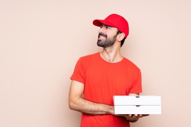 Jonge mens die een pizza over geïsoleerde gelukkig en achtergrond houdt houdt