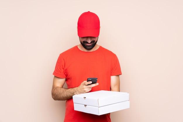 Jonge mens die een pizza over geïsoleerde houdt die een bericht met mobiel verzendt