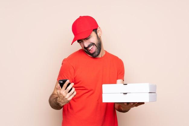 Jonge mens die een pizza over geïsoleerde muur met telefoon in overwinningspositie houdt