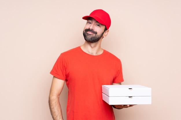Jonge mens die een pizza over het geïsoleerde muur lachen houdt