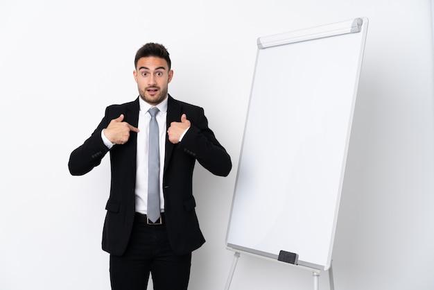 Jonge mens die een presentatie op wit bord en met verrassingsuitdrukking geeft