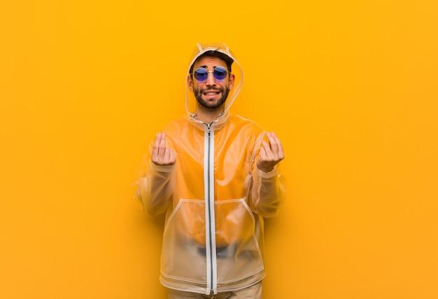 Jonge mens die een regenjas draagt die een gebaar van behoefte doet