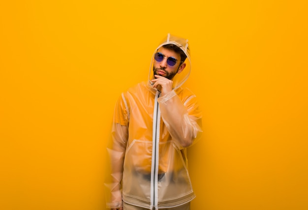 Jonge mens die een regenjas draagt die over een idee denkt