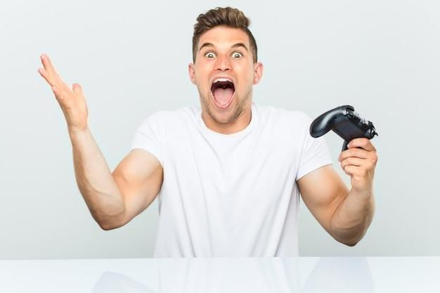 Jonge mens die een spelcontrolemechanisme houdt dat een overwinning of een succes viert
