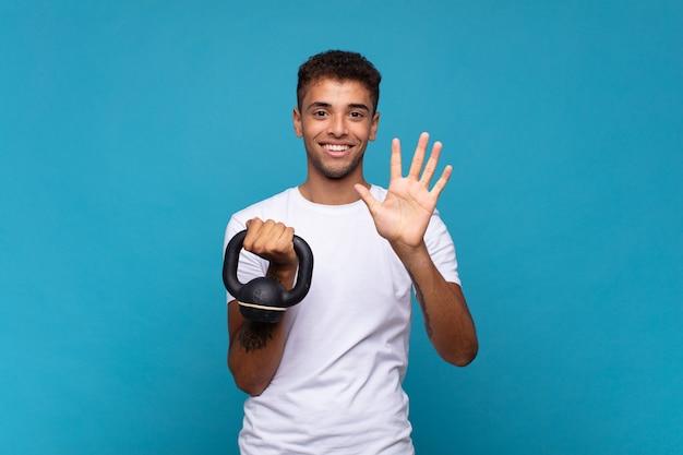 Jonge mens die een sumbbell opheft die vriendelijk glimlacht en kijkt, nummer vijf of vijfde met vooruit hand toont, aftellend
