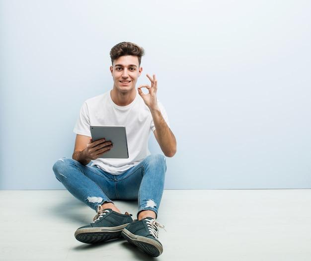 Jonge mens die een tablet houden die binnen vrolijk en zeker zittend tonend gebaar zitten.