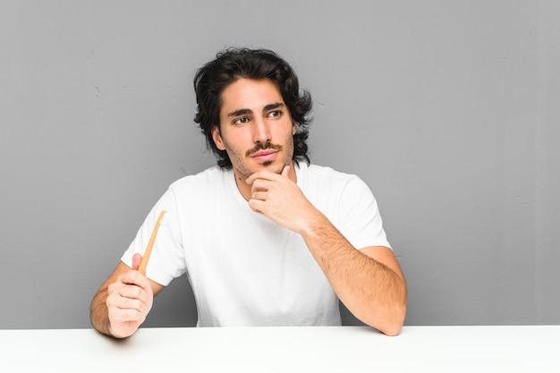 Jonge mens die een tandenborstel houdt zijdelings kijkend met twijfelachtige en sceptische uitdrukking.