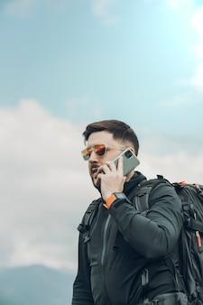 Jonge mens die een telefoongesprek maakt terwijl in de aard loopt