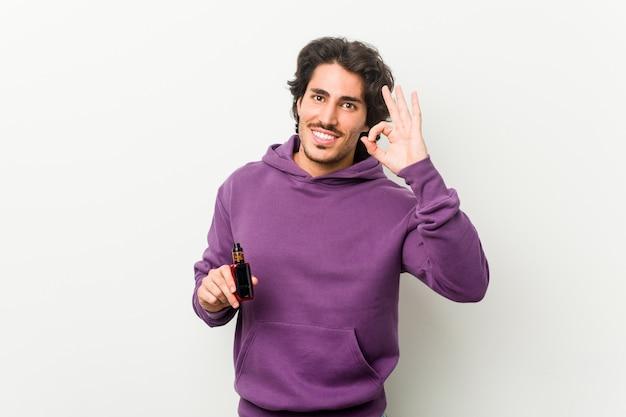 Jonge mens die een verdamper vrolijk en zelfverzekerd houdt die ok gebaar toont.