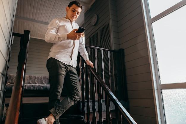 Jonge mens die een videogesprek van zijn mobiele telefoon voert. hij werkt vanuit huis