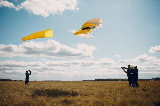 Jonge mens die een vlieger vliegt tegen blauwe hemel.