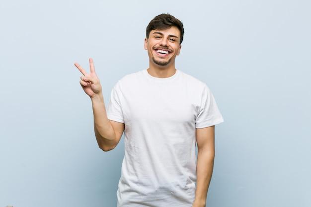 Jonge mens die een witte blij en onbezorgde t-shirt draagt die een vredessymbool met vingers toont