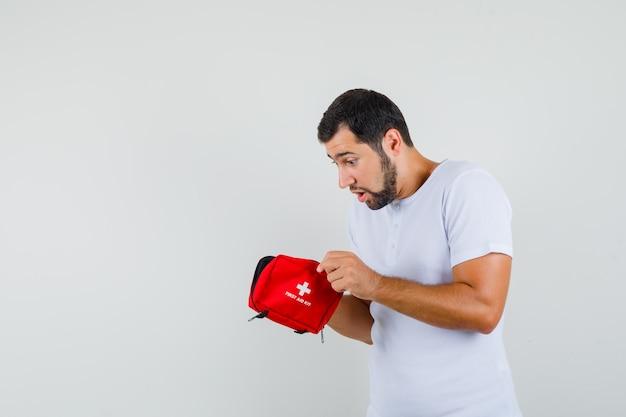 Jonge mens die ehbo-doos in wit t-shirt onderzoekt en geïnteresseerd kijkt. vooraanzicht. ruimte voor tekst