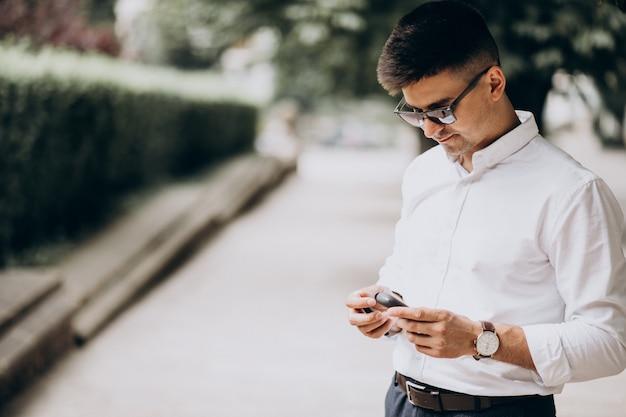 Jonge mens die elektrosigaret buiten in park roken