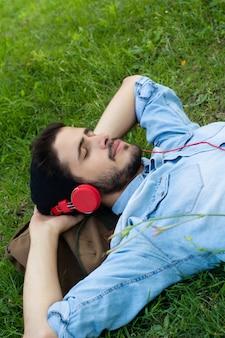 Jonge mens die en aan muziek op het gras ontspant luistert.