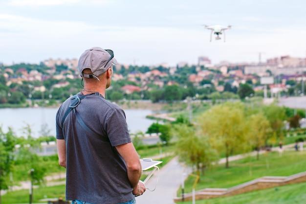 Jonge mens die en op een vliegende drone let navigeert